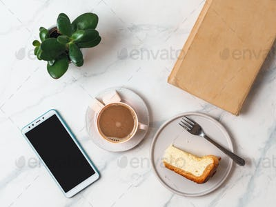 Coffee, cheescake, smartphone on tabletop