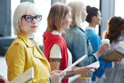 Blonde girl examining application form in line