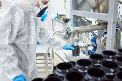 Factory worker filling plastic container with product