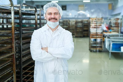 Confectionery factory employee standing and smiling