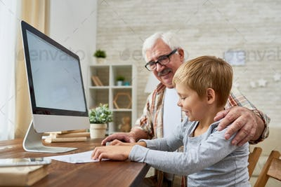 Grandfather and Little Boy using Computer