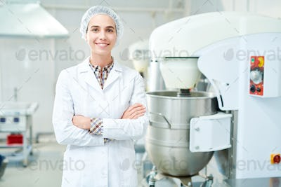 Smiling confectioner standing at factory