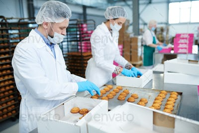Confectionery factory workers putting pastry into boxes