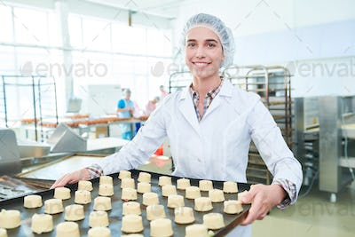 Female baker holding spacing with cakes