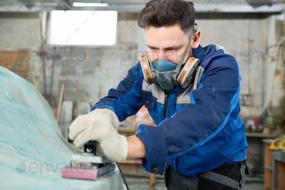 Man Polishing Motorboat in Workshop