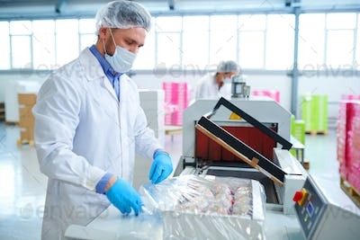 Confectionery factory employee wrapping box into packaging film
