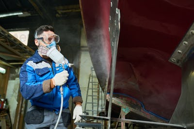 Worker Painting Boats in Yacht Workshop
