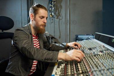 Bearded man in music recording studio