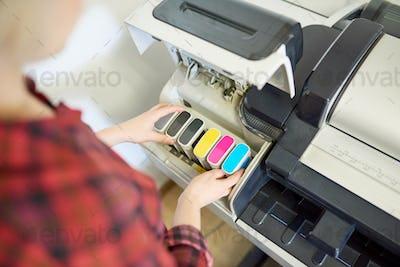 Crop woman putting ink in printer