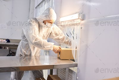 Factory worker taking ready package with product