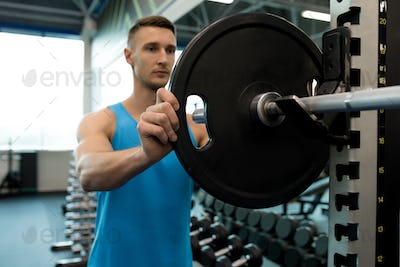 Man Assembling Barbell in Gym