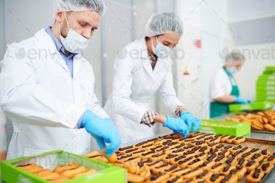 Confectioners making pastry with chocolate cream