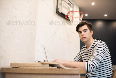 Thoughtful young man sitting at home using laptop