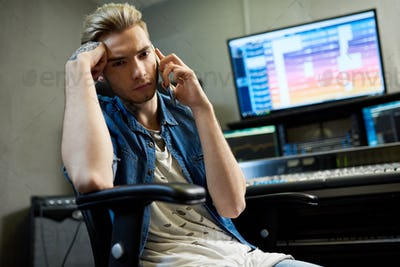 Stylish man speaking on phone in studio