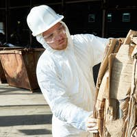Worker in Hazmat Suit Sorting Cardboard at Recycling Factory