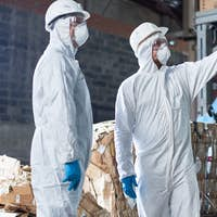 Workers in Hazmat Suits at Modern Factory
