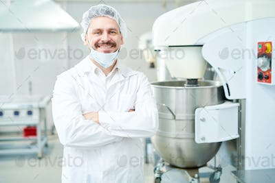 Confectionery factory worker standing and smiling