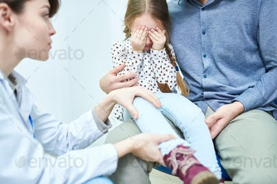 Scared little girl with close eyes by hands at doctor appointment