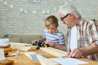 Grandfather and Little Boy Making Wooden Models Together