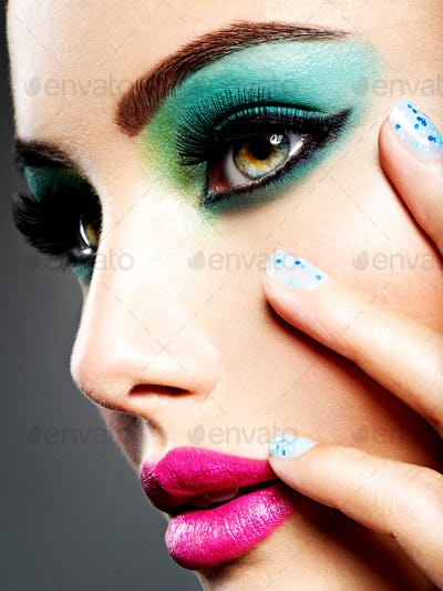 Face of a beautiful girl with fashion makeup and blue nails