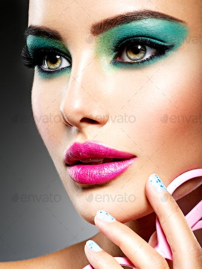 Beautiful Face of a woman with green vivid make-up of eyes