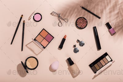 Set of makeup tools and accessory on pink background