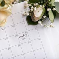 Choosing wedding date with pen writing heart on paper calendar