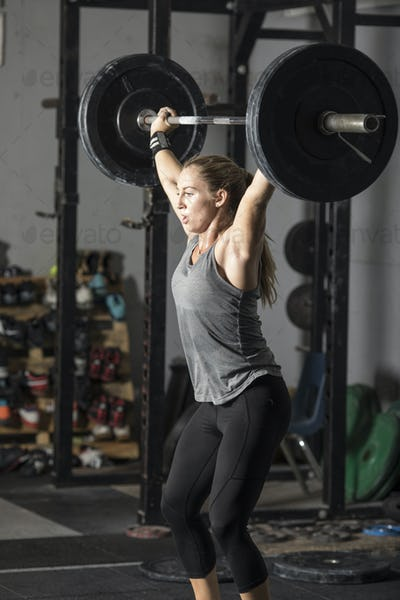 Young strong woman powerlifting in gym.