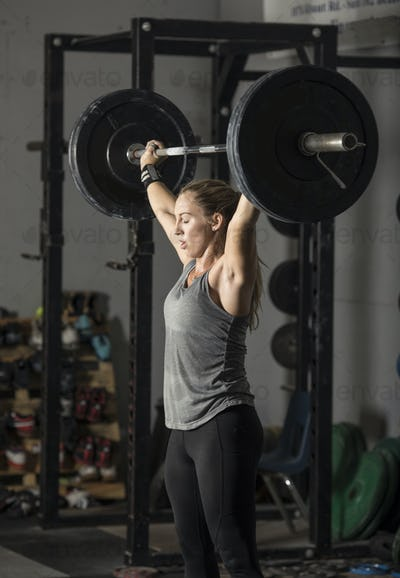 Strong young woman lifting heavy weights.