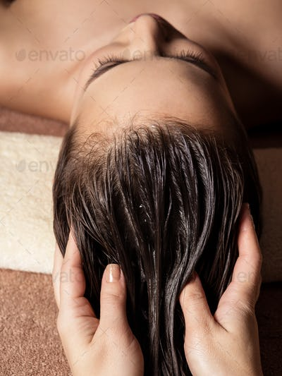 Cosmetologist massaging hair on the head of the woman. Spa treat