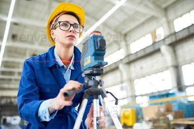 Smart woman using optical level at construction site