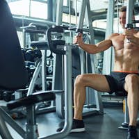 Muscular Man using Machines in Sports Club