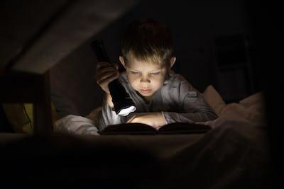 Cute Little Boy Reading with Flashlight