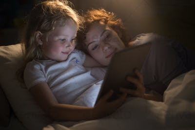 Cute Girl Reading E-Book with Mother