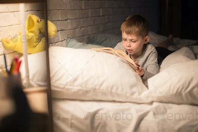 Cute Little Boy Reading Book at Night