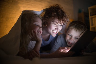 Young Mother Reading Stories with Two Kids