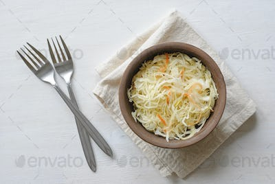 Two forks and bowl of raw cabbage on towel