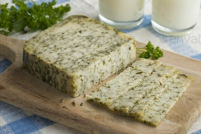 Piece of mature Dutch goats cheese with herbs