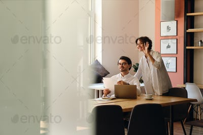Young smiling business colleagues with papers happily greeting someone at work in office