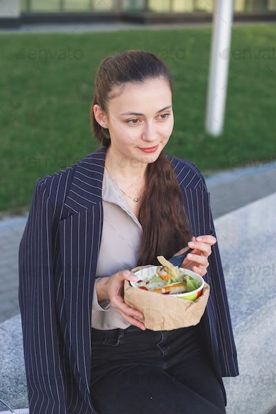 Business woman does not want to eat a salad with meat