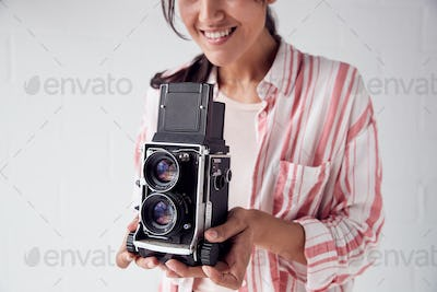 Female Photographer With Vintage Medium Format Camera On Photo Shoot Against White Studio Backdrop