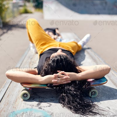 Young Woman Lying On Skateboard In Urban Skate Park