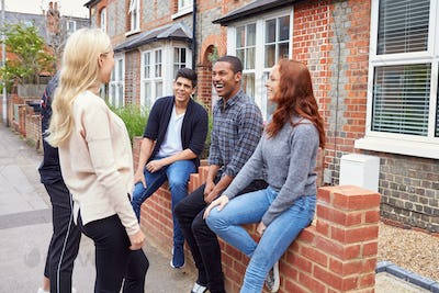 Group Of College Students Outside Rented Shared House Talking And Laughing