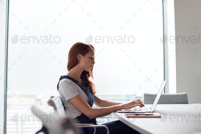 Casually Dressed Young Businesswoman Working On Laptop At Desk In Modern Workplace
