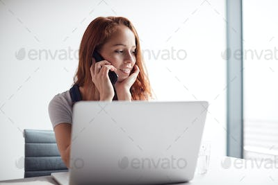 Casually Dressed Young Businesswoman Working On Laptop At Desk In Modern Workplace Making Phone Call