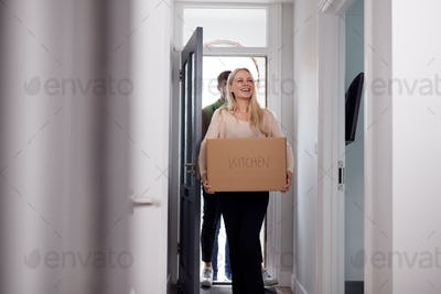 College Student Couple Carrying Boxes Moving Into Accommodation Together