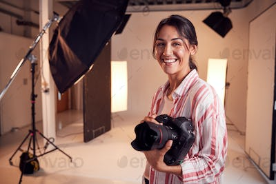 Portrait Of Smiling Female Photographer Standing In Studio With Camera And Lighting Equipment