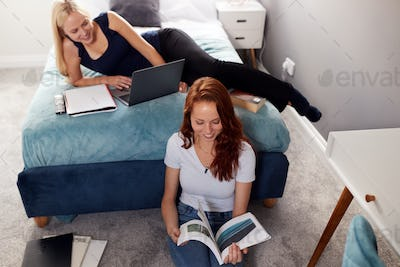 Two Female College Students In Shared House Bedroom Studying Together