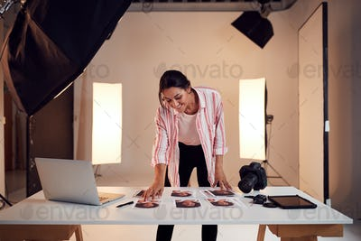 Female Photographer Editing Images From Photo Shoot In Studio