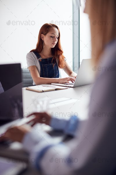 Two Casually Dressed Young Businesswomen Working On Laptops In Modern Meeting Room